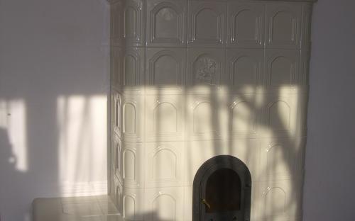 fényes beige kapumintás ülőpárkányos cserépkályha sarokba építve, Nádasd Kerámia